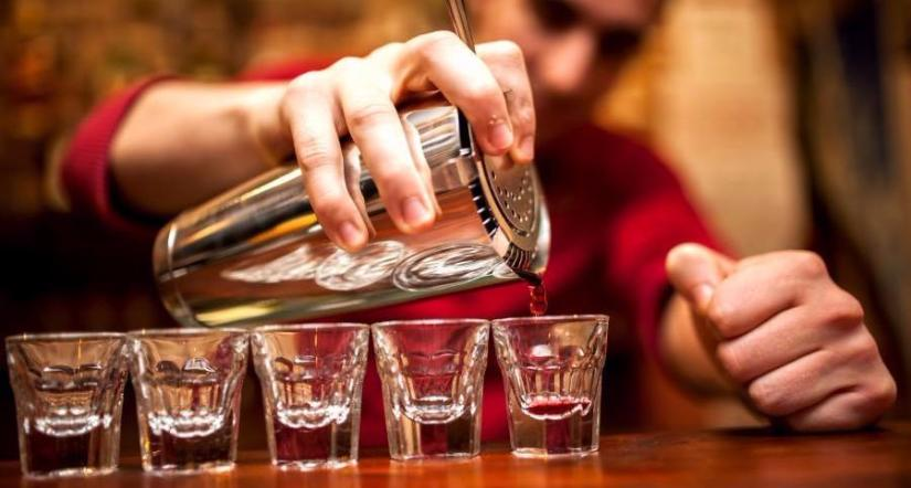 Bartending student pouring drinks into 5 shot glasses on finding bartending jobs page