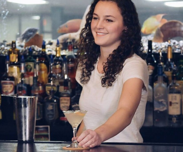 Student bartender behind the bar making a drink at Crescent School Gaming And Bartending